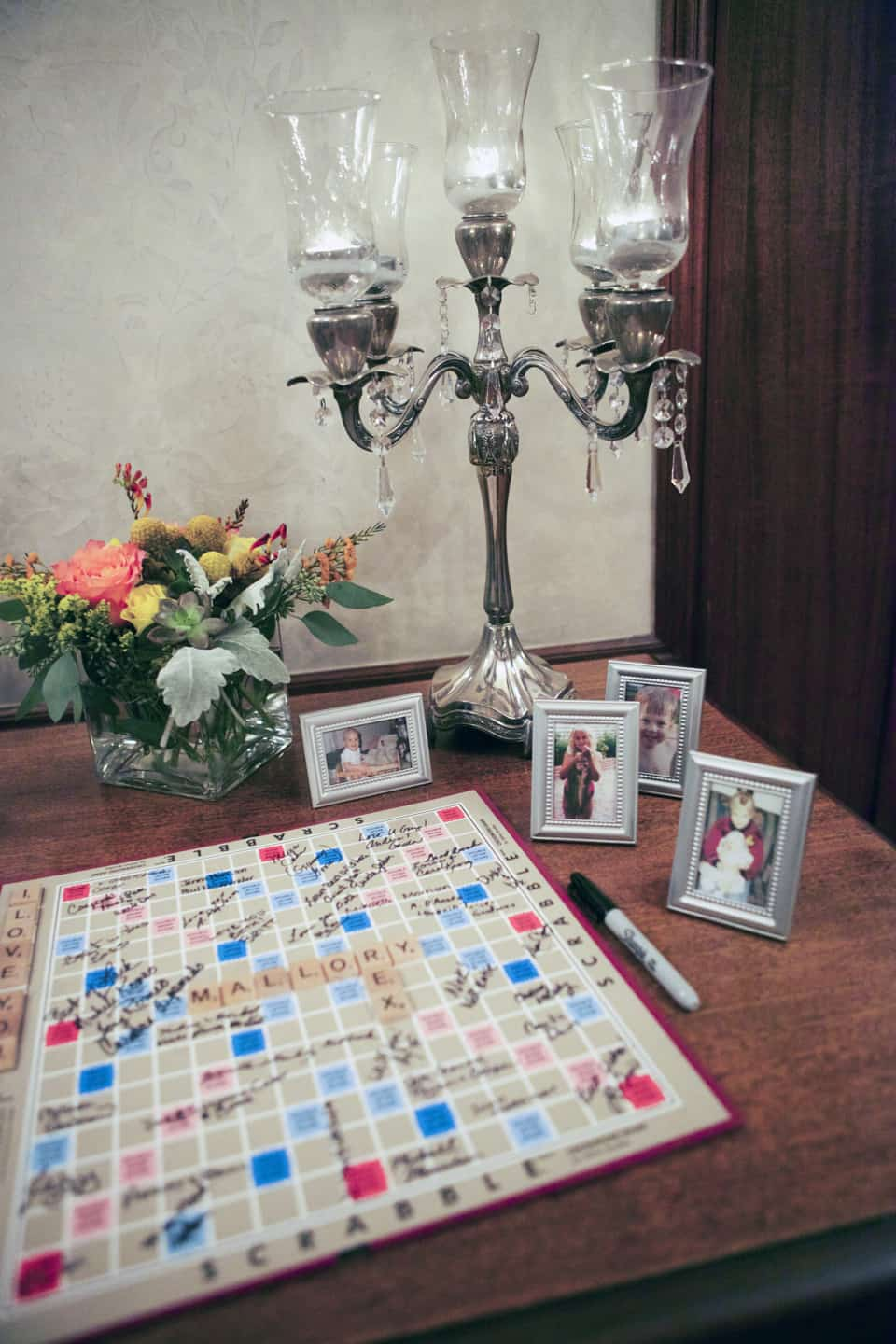 """Not only did the bride and groom provide board games for their guests who weren't that into dancing, they also incorporated their favorite game of scrabble into their guest book! You'll also notice framed photos of the bride and groom growing up for their guests to enjoy as they were waiting to sign the """"book""""!"""